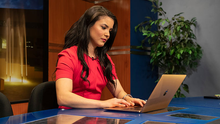 Student news anchor using laptop.